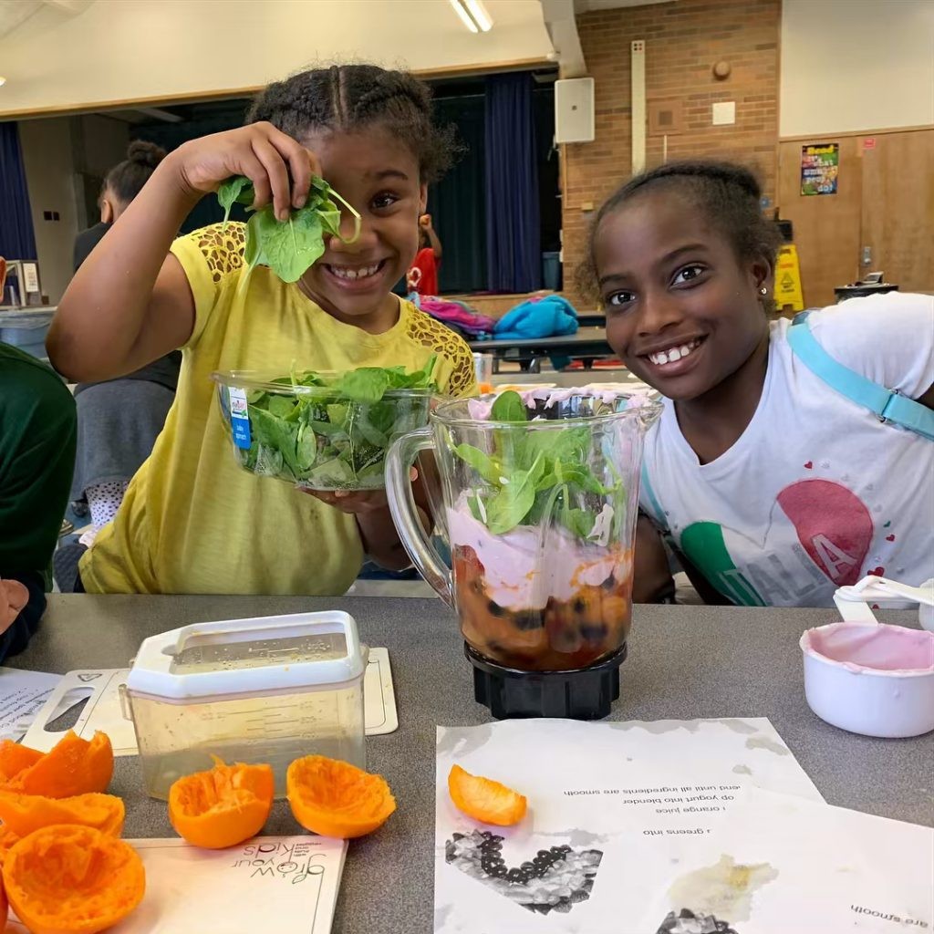 Woodward students add greens to a smoothie blender